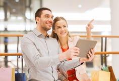 Coppie con il pc ed i sacchetti della spesa della compressa in centro commerciale Fotografia Stock Libera da Diritti