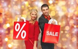 Coppie con il segno di vendita sui sacchetti della spesa Fotografie Stock