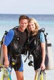 Coppie con l'attrezzatura di immersione con bombole che gode della festa della spiaggia Fotografia Stock Libera da Diritti