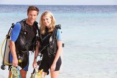 Coppie con l'attrezzatura di immersione con bombole che gode della festa della spiaggia Fotografie Stock Libere da Diritti