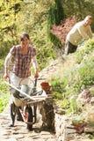 Coppie con la carriola che funziona all'aperto nel giardino Immagine Stock Libera da Diritti