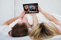 Coppie con la compressa digitale in camera da letto Immagini Stock