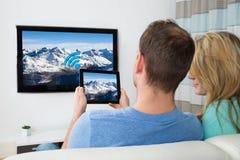 Coppie con la compressa digitale e la televisione nella sala fotografia stock libera da diritti