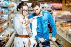 Coppie con la lista di compera lunga nel supermercato immagini stock libere da diritti