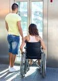 Coppie con la sedia a rotelle in elevatore Fotografie Stock