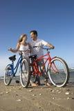 Coppie con le bici alla spiaggia Immagini Stock