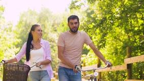 Coppie con le biciclette che camminano lungo il parco di estate stock footage