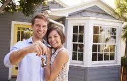 Coppie con le chiavi che stanno nuova casa esterna Fotografie Stock Libere da Diritti