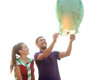 Coppie con le lanterne cinesi del cielo sulla spiaggia Fotografie Stock