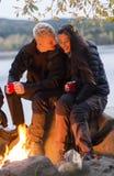 Coppie con le tazze di caffè che si siedono vicino al fuoco di accampamento Fotografia Stock Libera da Diritti