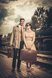 Coppie con le valigie sul binario della stazione ferroviaria Fotografia Stock Libera da Diritti