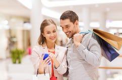 Coppie con lo smartphone ed i sacchetti della spesa in centro commerciale Immagini Stock Libere da Diritti