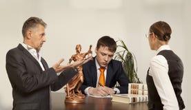 Coppie con scrittura del giudice allo scrittorio in tribunale Immagine Stock Libera da Diritti