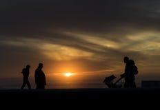 Coppie con un bambino che cammina nel tramonto sulla spiaggia immagini stock libere da diritti