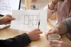 Coppie consultantesi dell'architetto, di agente immobiliare o del progettista con l'appartamento fotografia stock