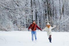 Coppie correnti allegre lungo la foresta coperta di neve durante le precipitazioni nevose Fotografie Stock