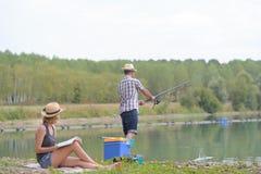 Coppie dalla lettura della donna di pesca dell'uomo del lago fotografie stock