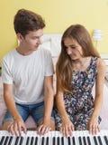 Coppie degli adolescenti che giocano sul piano elettronico immagine stock