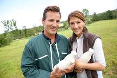Coppie degli agricoltori con le bottiglie per il latte fresche Fotografia Stock