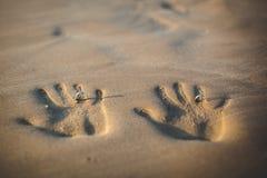 Coppie degli amanti ad un bello tramonto sopra l'oceano Coppie su una vacanza romantica Imprima le paia delle mani nella sabbia,  Fotografie Stock Libere da Diritti