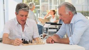 Coppie degli amici che giocano scacchi mentre i loro wifes stanno parlando stock footage