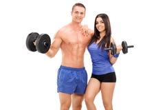 Coppie degli atleti che posano con i pesi del metallo Fotografia Stock
