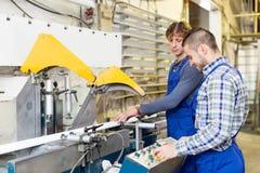 Coppie degli operai alla fabbrica Immagini Stock