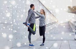 Coppie degli sportivi che allungano gamba all'aperto Immagini Stock