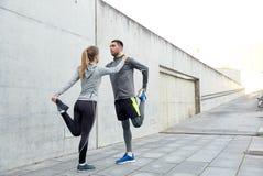 Coppie degli sportivi che allungano gamba sulla via della città Immagini Stock Libere da Diritti