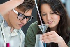Coppie degli studenti che lavorano all'aula di chimica Fotografie Stock