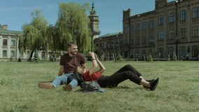 Coppie degli studenti che per mezzo del cellulare sul prato inglese della città universitaria stock footage