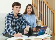 Coppie degli studenti che si siedono sul sofà e sui libri di lettura Immagine Stock