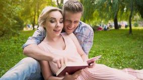 Coppie degli studenti nell'amore che si siede sulla coperta che leggono insieme libro educativo Immagine Stock Libera da Diritti