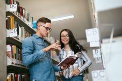 Coppie degli studenti nella biblioteca di istituto universitario Immagini Stock