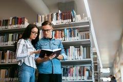 Coppie degli studenti nella biblioteca di istituto universitario Fotografia Stock Libera da Diritti