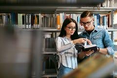 Coppie degli studenti nella biblioteca di istituto universitario Fotografie Stock Libere da Diritti