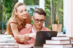 Coppie degli studenti in una biblioteca Immagini Stock Libere da Diritti
