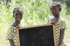 Coppie dei bambini africani che stanno all'aperto con una grande lavagna Fotografia Stock Libera da Diritti
