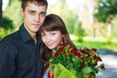 Coppie dei bei amanti del ritratto giovani con un mazzo del ROS rosso Immagine Stock Libera da Diritti