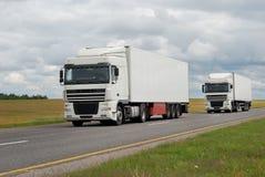 Coppie dei camion bianchi sulla strada principale Fotografie Stock