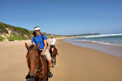 Coppie dei cavalieri del cavallo sulla spiaggia Immagini Stock