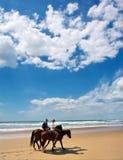Coppie dei cavalieri sulla spiaggia sotto i cieli drammatici Fotografia Stock