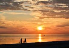 Coppie dei ciclisti che camminano lungo la spiaggia fotografia stock libera da diritti