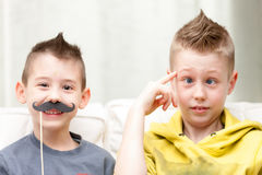 Coppie dei fratelli piccoli che fanno i fronti divertenti immagini stock