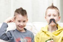 Coppie dei fratelli piccoli che fanno i fronti divertenti fotografia stock