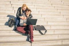 Coppie dei giovani dei pantaloni a vita bassa con il computer portatile del computer in punto urbano Immagine Stock