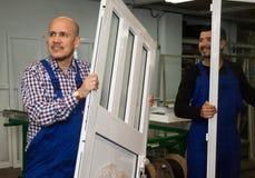 Coppie dei lavoratori che consegnano i profili del PVC Fotografia Stock
