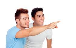 Coppie dei migliori amici che indicano qualcosa Fotografie Stock Libere da Diritti