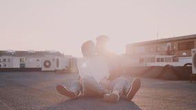 Coppie dei pantaloni a vita bassa al tramonto sul tetto stock footage