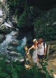 Coppie dei pantaloni a vita bassa che fanno un'escursione sui precedenti di un fiume della montagna Fotografia Stock